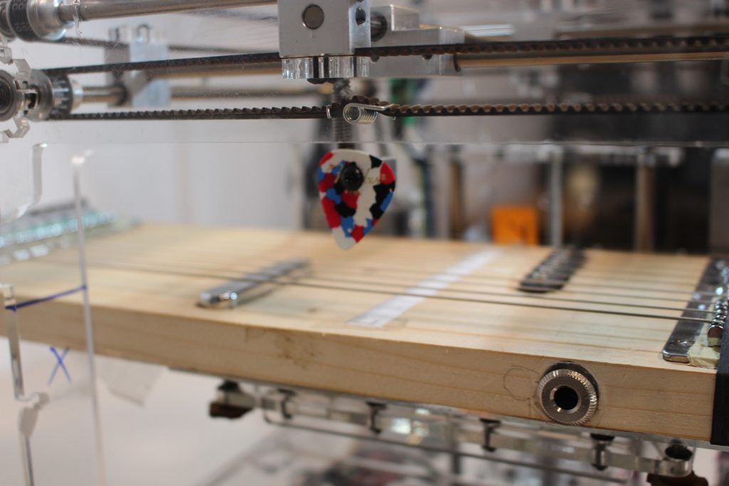 Ein Plektrum, welches an einem gepimpten 3D-Drucker befestigt ist, schwebt über einer selbstgebauten Zither.
